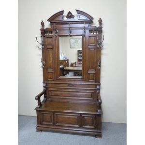 A substantial French Henri II panelled oak hallstand featuring a wide settle bench with storage and retaining all original...