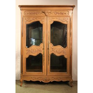 Well carved blond cherrywood Marriage armoire in the Louis XV manner. The shaped doors and sides infills in bevel edged crystal...