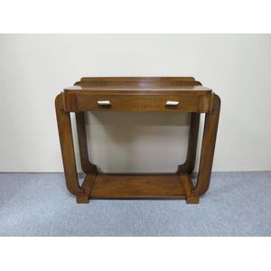 French Art Deco side table in figured walnut with a frieze drawer retaining the original brass handles that feature a low and...