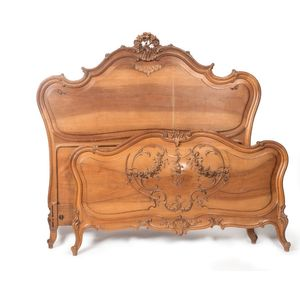 A 19th century Louis XV French double bed. The matching moulded walnut panelled head and foot, raised on short cabriole legs,...