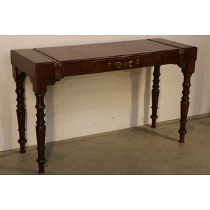 A walnut and cigar leather writing table in the Regency Georgian manner. The whole leather covered faux suitcase top with...