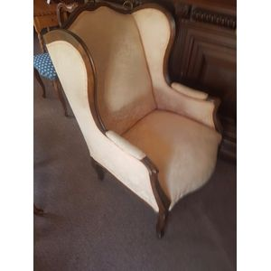 French wingback ararmchair tastefully covered  in apricot colored brocade .Comfortable  and in great condition  .