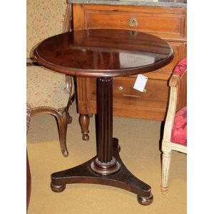 This George III period, Regency wine table is made of dark, dense Cuban mahogany. The circular top is supported by a reeded...