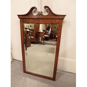 An English figured walnut wall mirror featuring a broken swan neck pediment. In good, detailed condition.