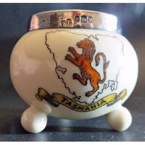 A small 3 footed pot; souvenir of Tasmania with a sterling silver mount hallmarked for London 1909 and makers mark