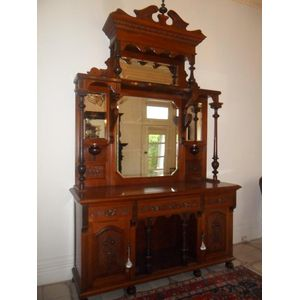 Edwardian walnut sideboard with original  carved top and in exellent condition.