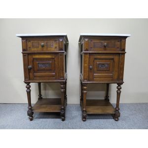 Pair of French carved and panelled bedside cabinets in oak, retaining the original white marble tops. In detailed condition....