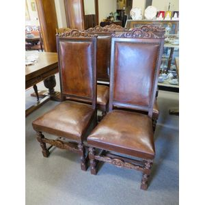 Set of 6 French high-back oak dining chairs featuring carved top rails and retaining the original leather upholstery and stud...