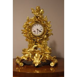 French  rococo heavy gilded bronze clock adorned with cherubs and in the most beautiful condition. A glazed watch glass covers...