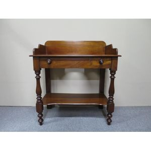 An English mahogany 2-tier washstand with a low back and turned front supports. Circa 1870.