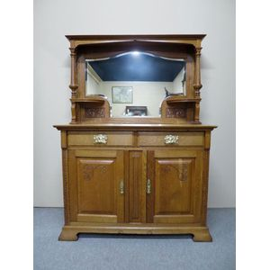 English Art Nouveau 2-door sideboard in golden oak, retaining the original shaped and bevelled mirror. In detailed condition....