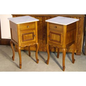 An antique pair of solid walnut or pale mahogany bedside tables in the French Louis XV rococo manner. Each with a single drawer...
