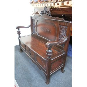 Grand Australian tudor hall seat with scroll decorative arms, carved floral panels, carved crest. Has lift up lid for storage,...