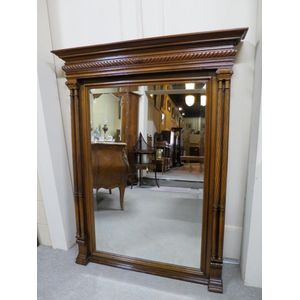 French Henri II wall mirror flanked with twin columns and featuring a finely detailed moulded and carved cornice. Circa 1900.