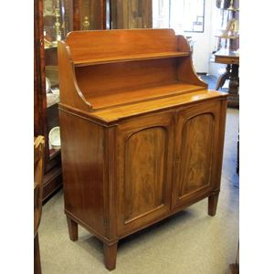 A delightful English, George III, Regency, neoclassical mahogany chiffonier of small size. The arched paneled doors hide a...