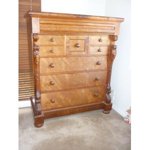 A late 19th century full huon pine chest of 8 drawers with features of elaborate carved corbels and scrols, round knobs, a...
